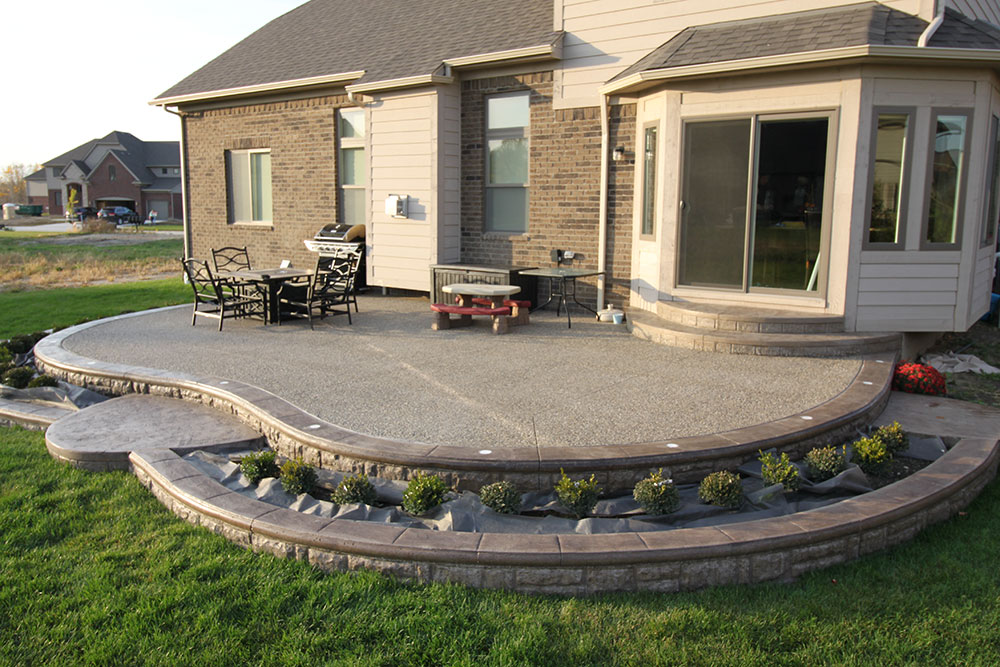 Exposed aggregate patio with retaining wall by Biondo Cement